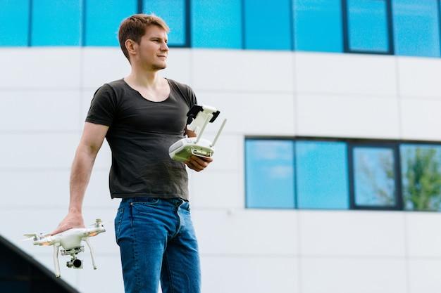 Мужчина держит дрон на открытом воздухе