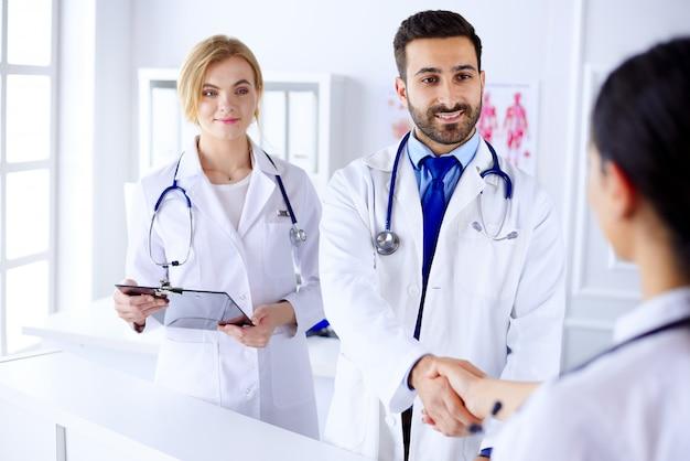 若いアラブ医師は病院で看護師と握手します。人体の背景