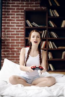 Молодая и красивая девушка играет на консоли на кровати у себя дома