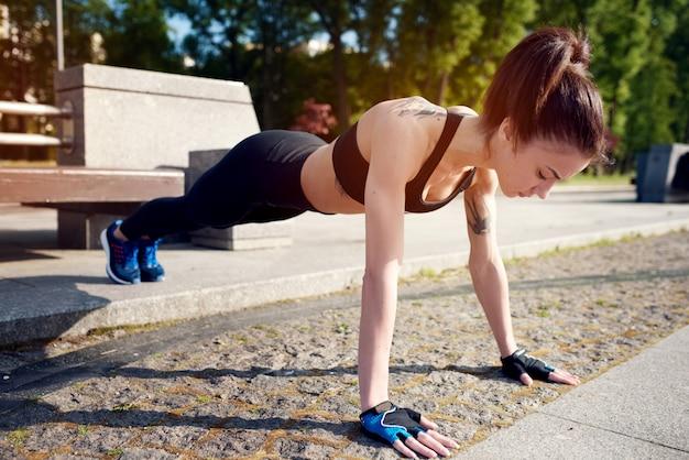 Молодая красивая и сильная женщина, делать отжимания в парке в летнее время. спортивная концепция. здоровый образ жизни