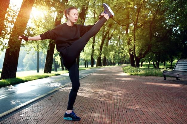 Молодая красивая и сильная женщина активно делает физические упражнения в парке летом. спортивная концепция. здоровый образ жизни