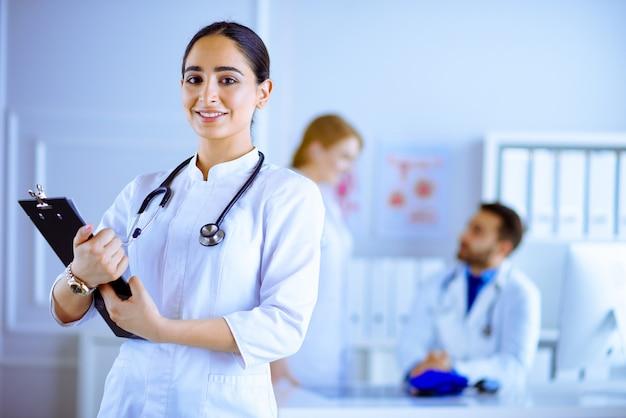 病院で彼女のチームの前に立っている女性のアラビアの医者