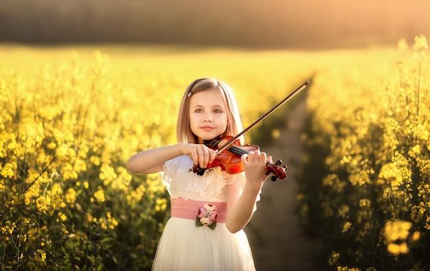 夏のフィールドでバイオリンを持つ少女