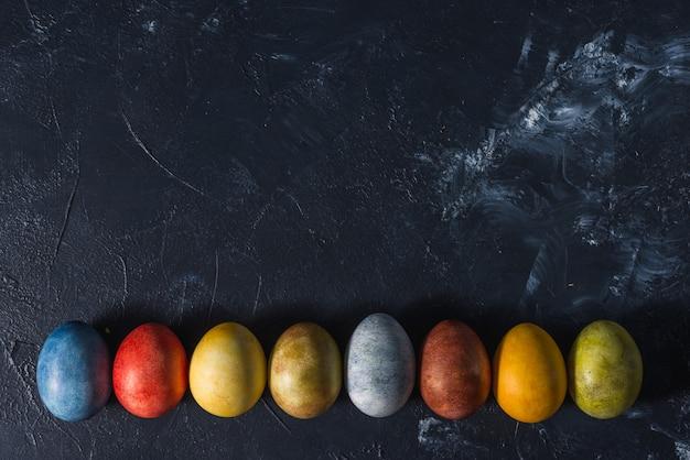 Разноцветные яркие пасхальные яйца. пасхальные яйца на темном фоне.