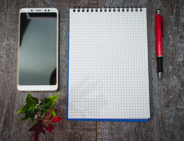 ビジネスノートと木製のテーブル上のペン