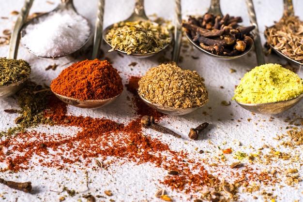 Различные специи молотый куркума перец имбирь корица трава приправа соль паприка тмина на столе. вид сверху. ароматные индийские специи