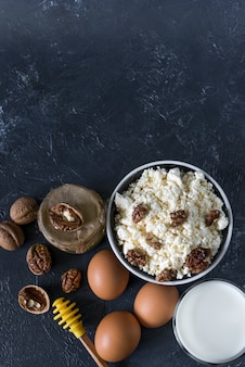 Концепция здорового питания, домашний творог, стакан молока, йогурт и куриные яйца на фоне камня, молочные продукты