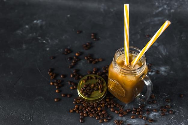 暗闇の中で氷で冷たいおいしい芳香族コーヒーのグラスに牛乳を注ぐ