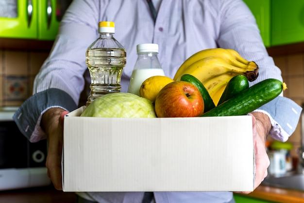 Пожертвование коробки доставки еды концепция пожертвования пищи. мужчина держит ящик для пожертвований с овощами, фруктами и другой едой для людей