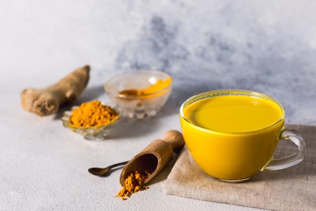 スパイスシナモンと食材と白い表面に黄金のウコンミルク