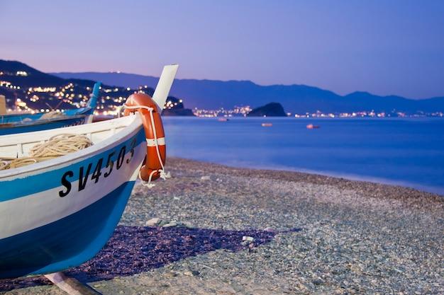 Лодка на пляже ноли на закате