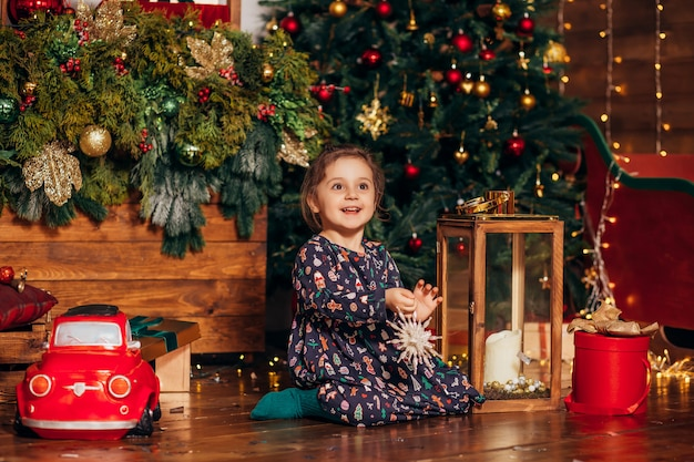 Маленькая девочка наряжает елку дома