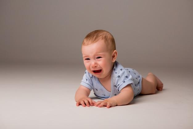 泣いている赤ちゃんは明るい背景に分離します。