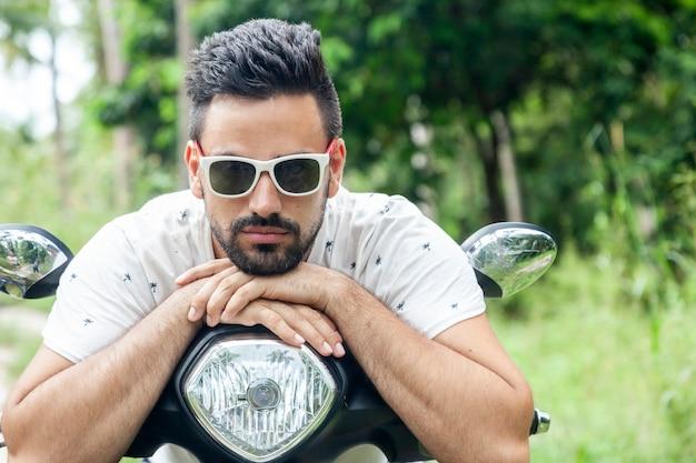 ジャングルの中でバイクで魅力的なスタイリッシュな混血の若い男