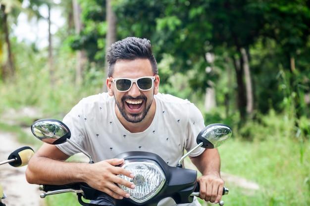 ジャングル、休日、幸福のバイクで魅力的な幸せな笑みを浮かべて混血の若い男