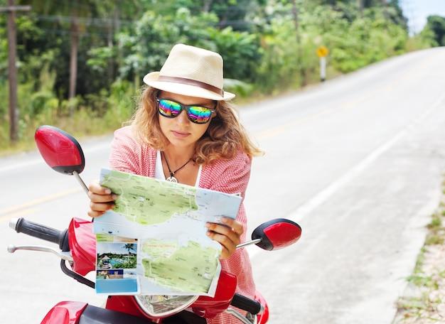 Красивая молодая женщина с картой в руке и мотоцикл на дороге. путешествия, навигация, туризм