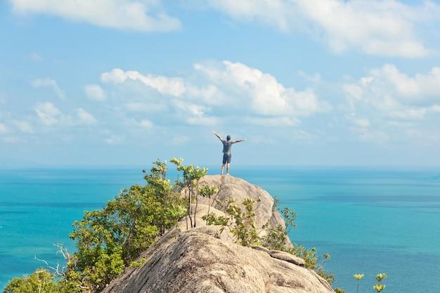 海を見下ろす丘の上に立っている人。ターコイズブルーの海の平面図。旅行と休暇。