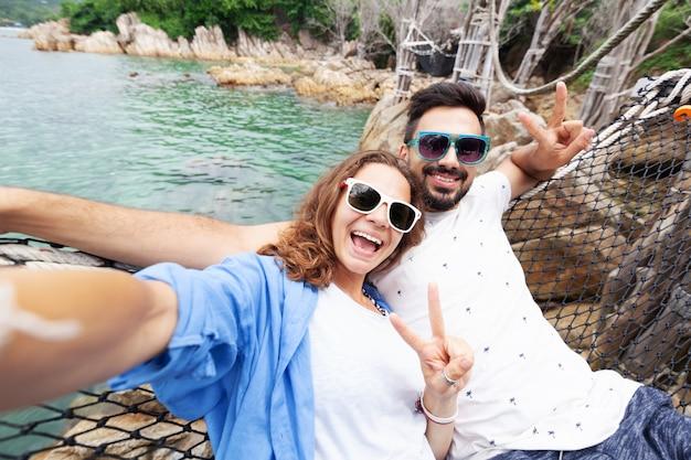 Молодая красивая счастливая улыбающаяся смешная пара мужчина и женщина лучшие друзья в гамаке на отдыхе делает селфи на смартфоне на фоне моря