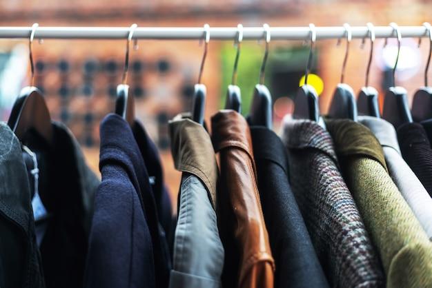 Одежда на вешалках на барахолке, концепция одежды по низким ценам, имидж с мягким фокусом