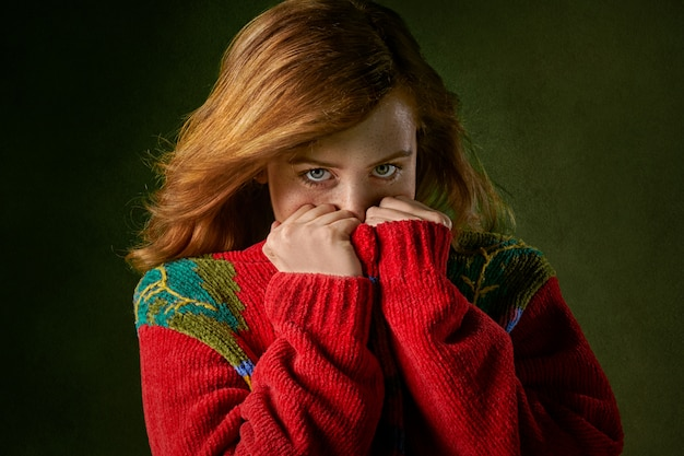 セーターで口を覆っている女性