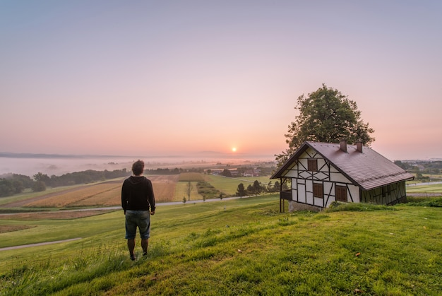昼間の家と木の近くに立っている人
