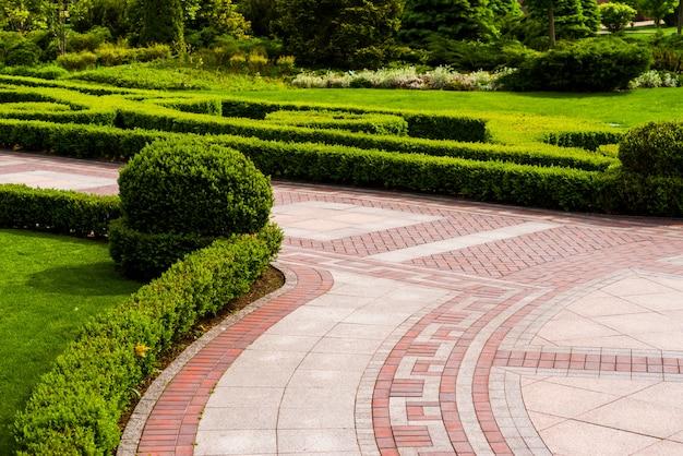 ランドスケープデザインの緑の茂みと石のタイルの通路