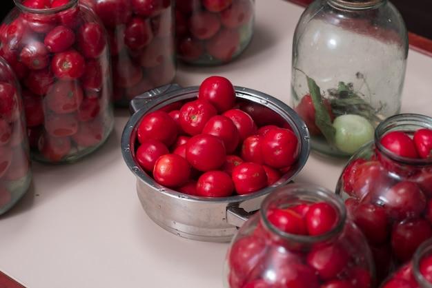 Помидоры, приготовленные для консервирования в стеклянных банках