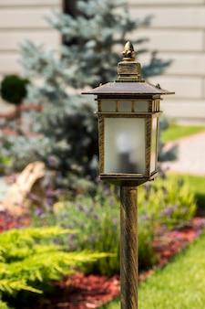 Уличный фонарь в саду, на фоне клумбы