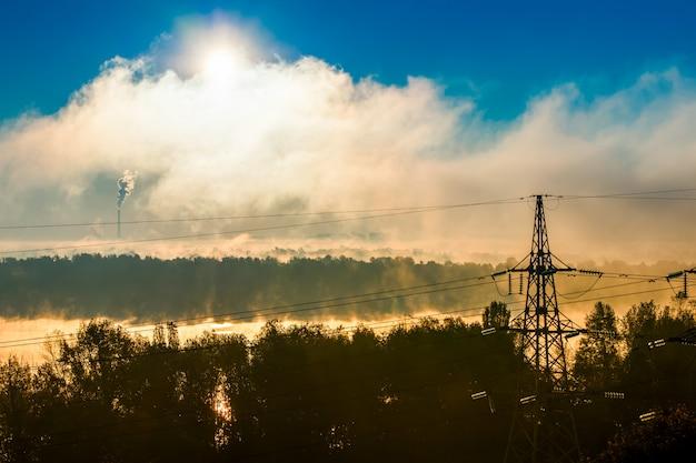 夜明けの霧の中の高電圧電気タワー