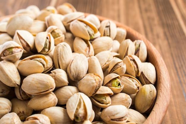 Раздели спелые фисташковые орехи в миску на деревянном столе