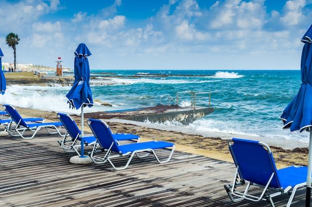 ビーチにデッキチェア、青いサンベッドがある海辺の遊歩道のビーチ