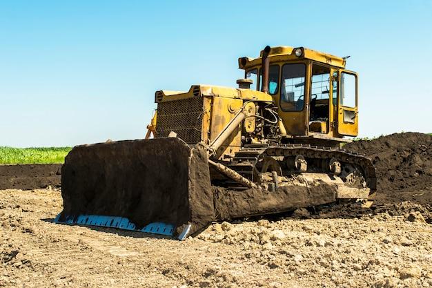 Желтый бульдозер трактор стоит в поле