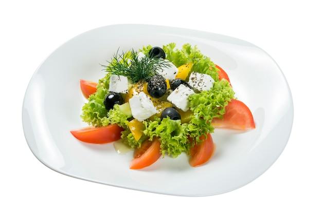 Греческий салат на тарелке на белом фоне