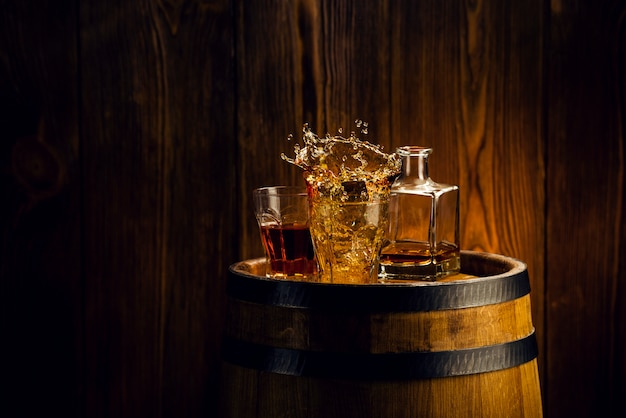 Коньяк в бокалах, в деревянном бочонке, в погребе всплеск алкоголя в бокале