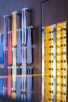 Солнцезащитные очки на полке и галстуки на вешалках
