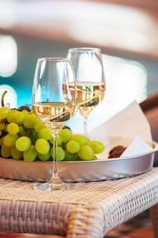 トレイ上のブドウの近くのグラスでワイン