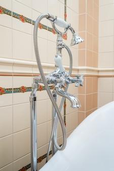 パイプバスルームと洗面台に蛇口とホースが付いたシャワー