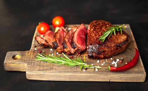 牛肉のグリルステーキ、ハーブ、スパイス、石の背景、トップビューでまな板の上