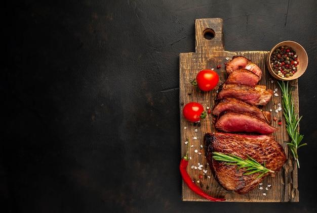 牛肉のグリルステーキ、ハーブ、スパイス、石の背景、テキストのコピースペース平面図。
