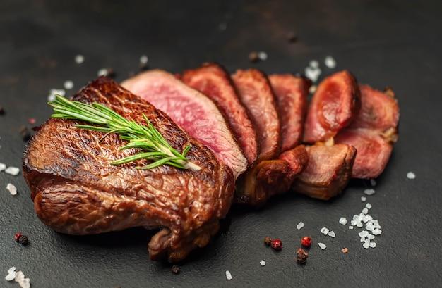牛肉のグリルステーキ、ハーブ、スパイス、石の背景、上面図