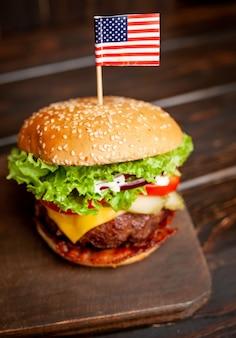 Вкусный свежий домашний бургер с американским флагом на деревянный стол