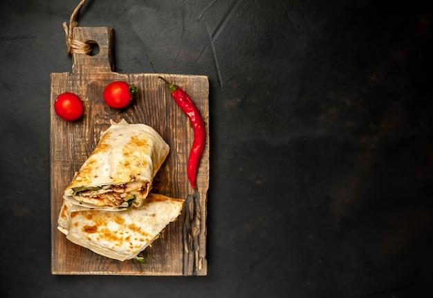Обертывания буррито с курицей и овощами на разделочной доске, на фоне бетона, мексиканская шаурма
