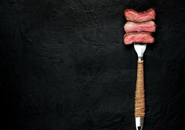 Стейк из говядины на вилке на темном бетоне
