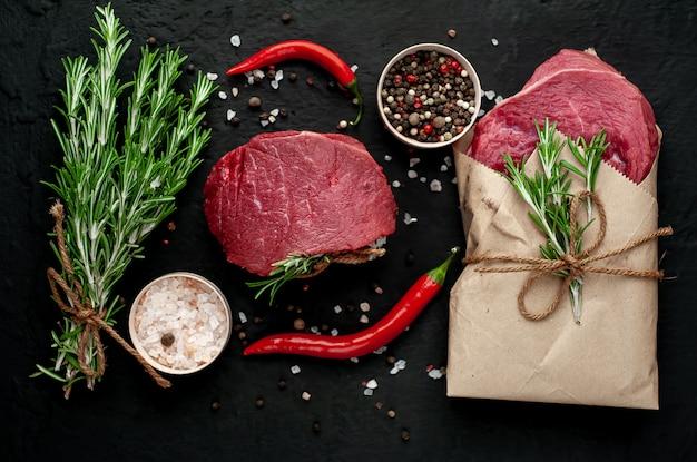 Мясо из мясной лавки, два стейка с ингредиентами. два куска говядины на черном бетоне