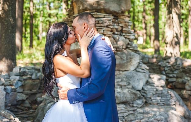 Жених и невеста в парке в солнечный день, влюбленная пара целуется на природе