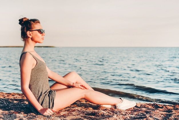 Молодая девушка в легком платье и темных очках сидит на песке и смотрит на море