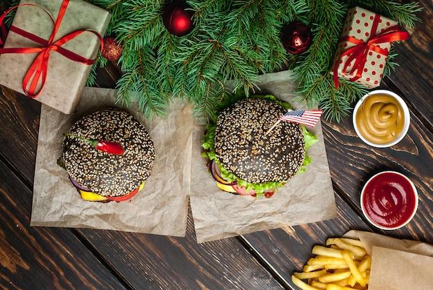 Два рождества черный гамбургер с картофелем фри черный, салат, помидоры и картофель. деревянный фон