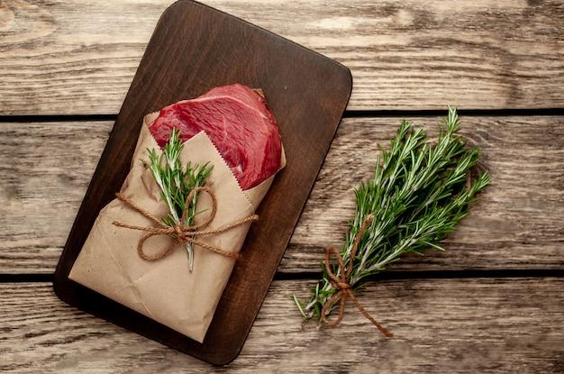 Мясо из мясной лавки, завернутые в бумагу. кусок говядины на дереве с различными специями в деревенском стиле