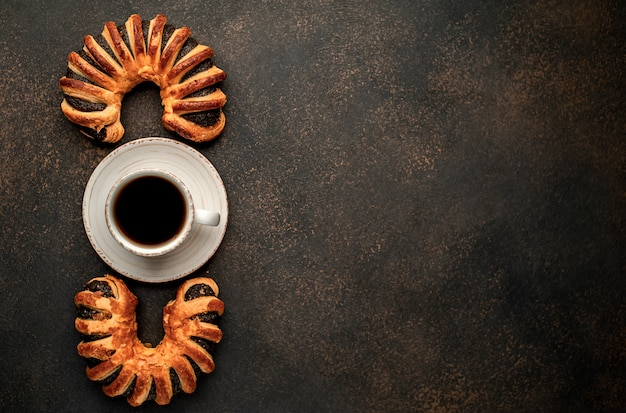 コーヒーと焼きたてのペストリー、テキストのコピースペースと石の背景にジャムとベーグル