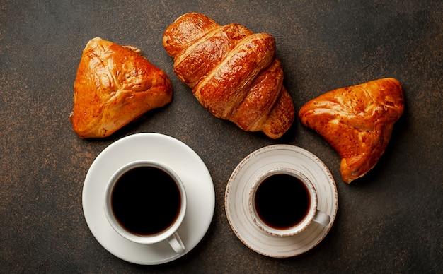 Два кофе и круассан, хлебобулочные изделия на фоне камня. вкусный завтрак